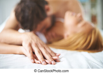 Cuddling - Hands of female and male lying on bed