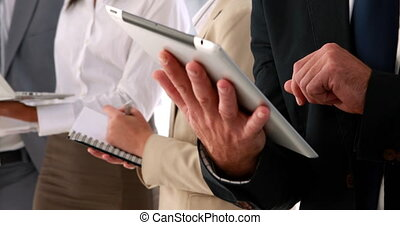 Business people using tablet pc - Business people standing...
