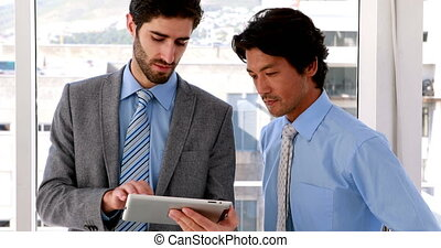 Businessman using tablet pc with his colleague in the office