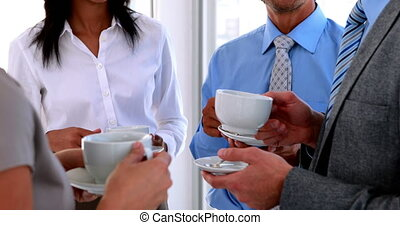 Business team having coffee and chatting in the office