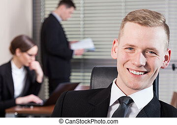 Smiling businessman and his co-workers during work