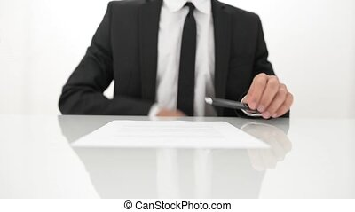 Businessman signing a contract on a white table.