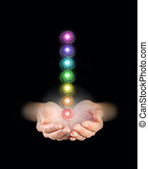 Holding Seven Chakras - Hands emerging from darkness, cupped...