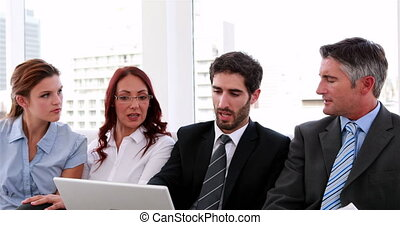 Business team sitting on couch having a meeting using laptop...