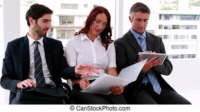 Business team sitting on chairs discussing their work in the...