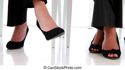 Businesswomen shaking their feet nervously in the office