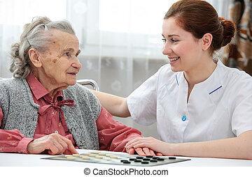 Senior woman playing checkers with a nurse in a retirement...