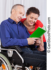 Disabled and a nurse reading a book together - A disabled...