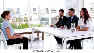 Interview panel speaking with young applicant and shaking...
