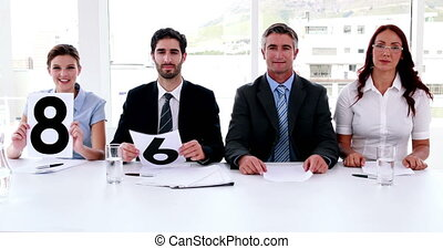 Interview panel holding up scores in the office