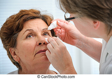 Senior woman applying eye drops - Doctor helps the patient...