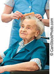 Hair care - Caregiver dressing the hair of a senior woman....
