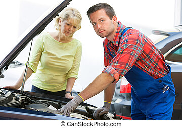 Auto repair shop - Auto mechanic and female customer in auto...