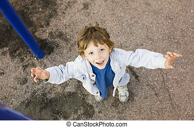 little cute boy hanging on gymnastic ring, playground...