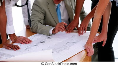 Architects looking at blueprints - Team of architects...