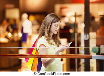 Shopping girl with smartphone - Smiling girl with smatphone...