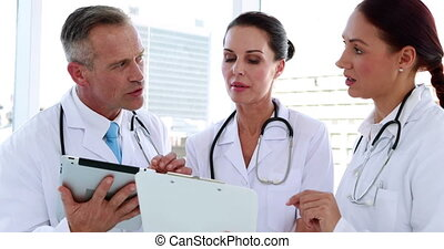 Team going over a file together - Medical team going over a...
