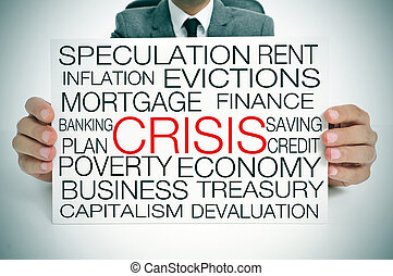 economic crisis - a businessman holding a signboard with...