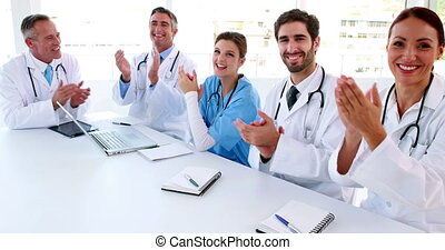 Medical team clapping during a meeting in the board room at...