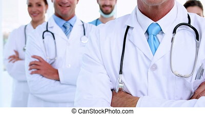 Doctor smiling at camera with team behind him at the...