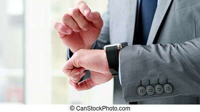Businessman using his smart watch in his office