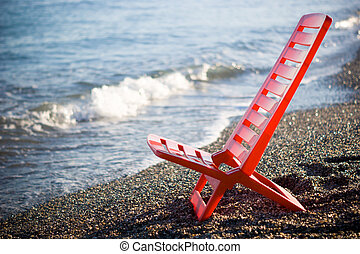 Red deck chair at the beach - close up of a red chair in the...