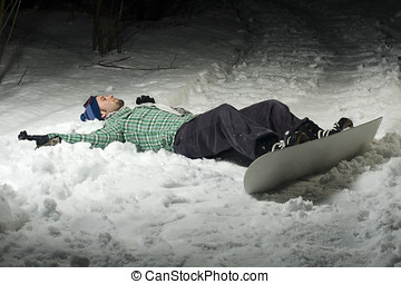 Snowboarder laying in snow because he\'s tired