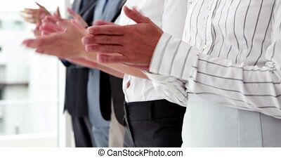 Business team standing in a line clapping in the office