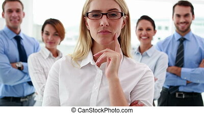 Businesswoman looking at camera with colleagues behind her...