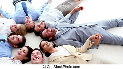 Business people lying in a circle holding hands in the...