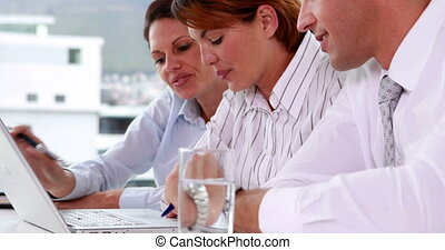 Business team working together at a meeting with laptop in...