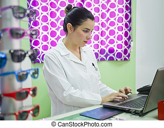 Optical store, people and lenses - Young professional woman...