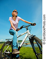 Young woman is sitting on her bicycle - Young happy woman is...