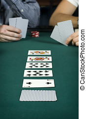 Line up of cards on poker table with player in background