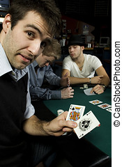 Man holding winning hand in poker - Young man holding...