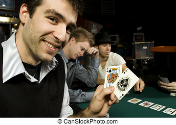 Young poker player holding winning hand in bar