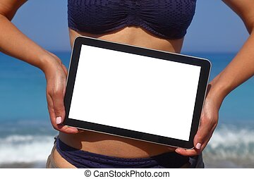Woman holding tablet computer on the beach