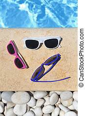 Colorful sunglasses by the poolside