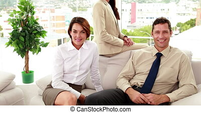 Business people sitting on couch smiling at camera in the...