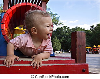 Happy kid in a playground tunnel - A joyful kid is sticking...