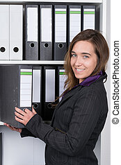Woman is taking a file out of a shelf - A young smiling...