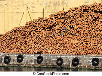 Pile of pinewood timber with building in background