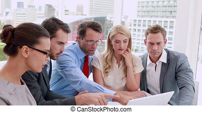 Business people working together at meeting on laptop in the...