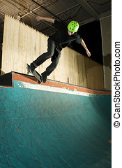 Skateboarder doing a grind on ramp in skatepark