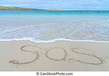 SOS distress sign written in sand of tropical island beach...