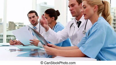 Medical team looking at xray and files during meeting at the...