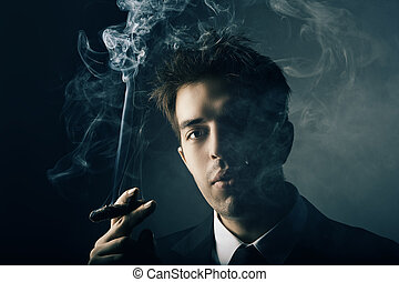 Young handsome stylish man smoking cigar, Fashion portrait