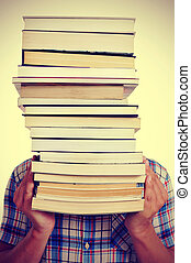 man with books, with a filter effect - a young man holding a...