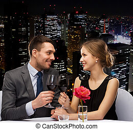 young couple with glasses of wine at restaurant -...