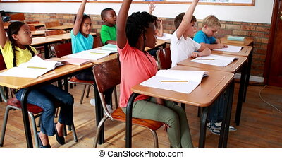 Pupils raising their hands during class in elementary school